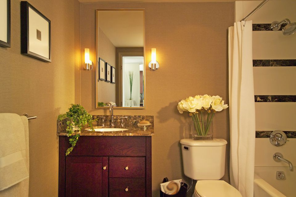 Wooden cabinet and mirror with wall sconces in domestic bathroom