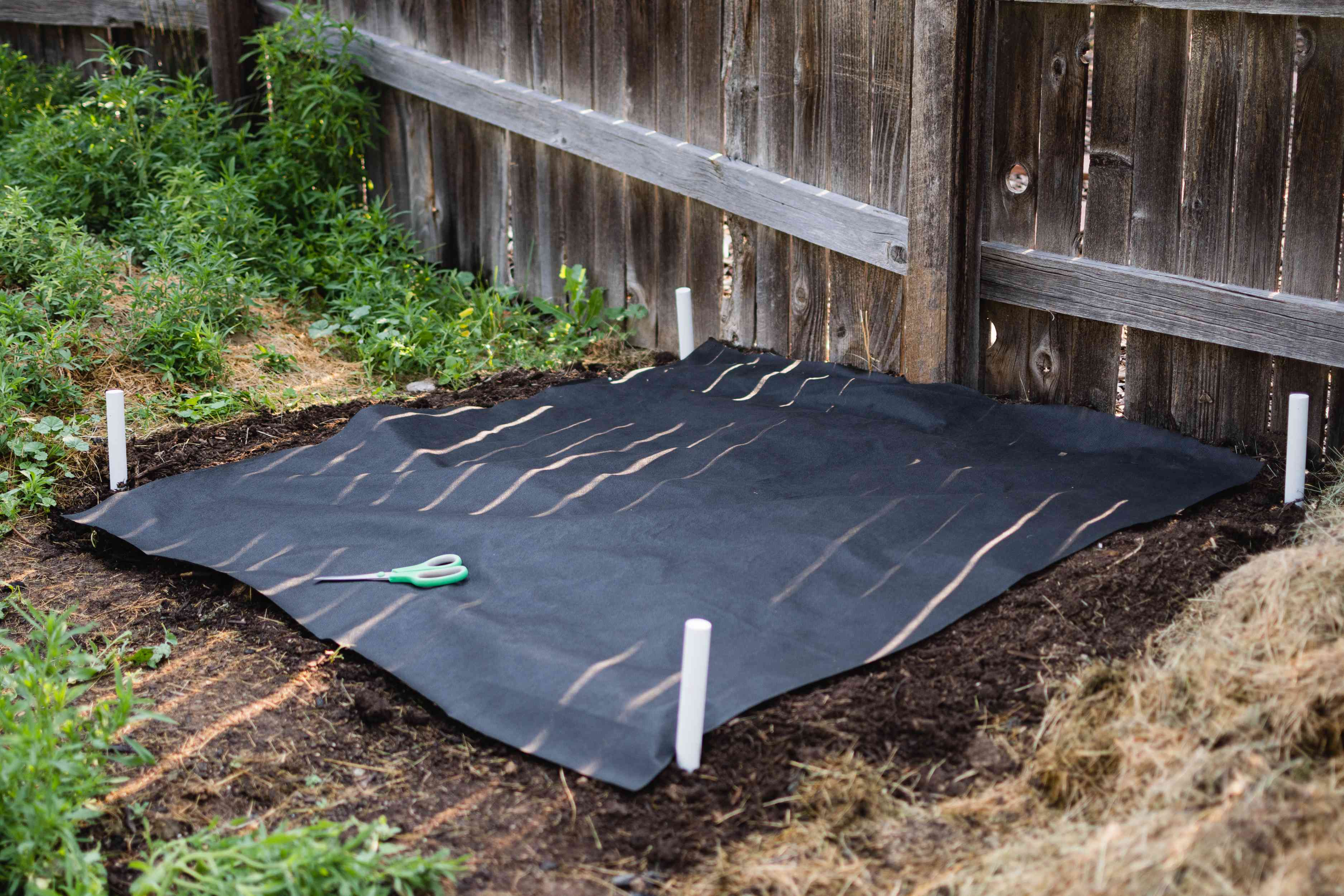 Weed cloth cut over composting pile location with green scissors on top