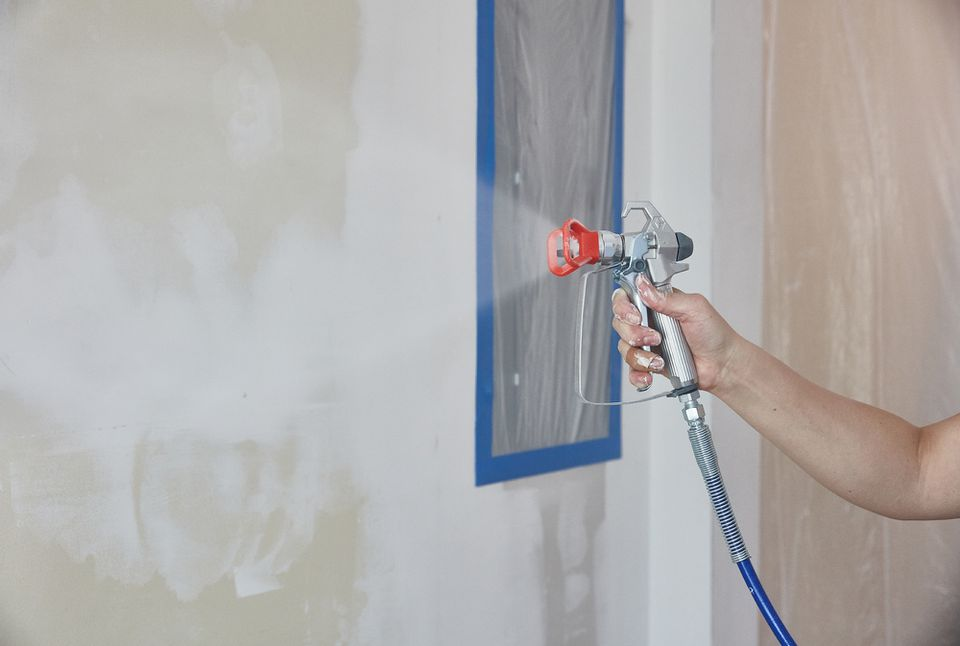 Paint sprayer spraying white paint on unfinished wall