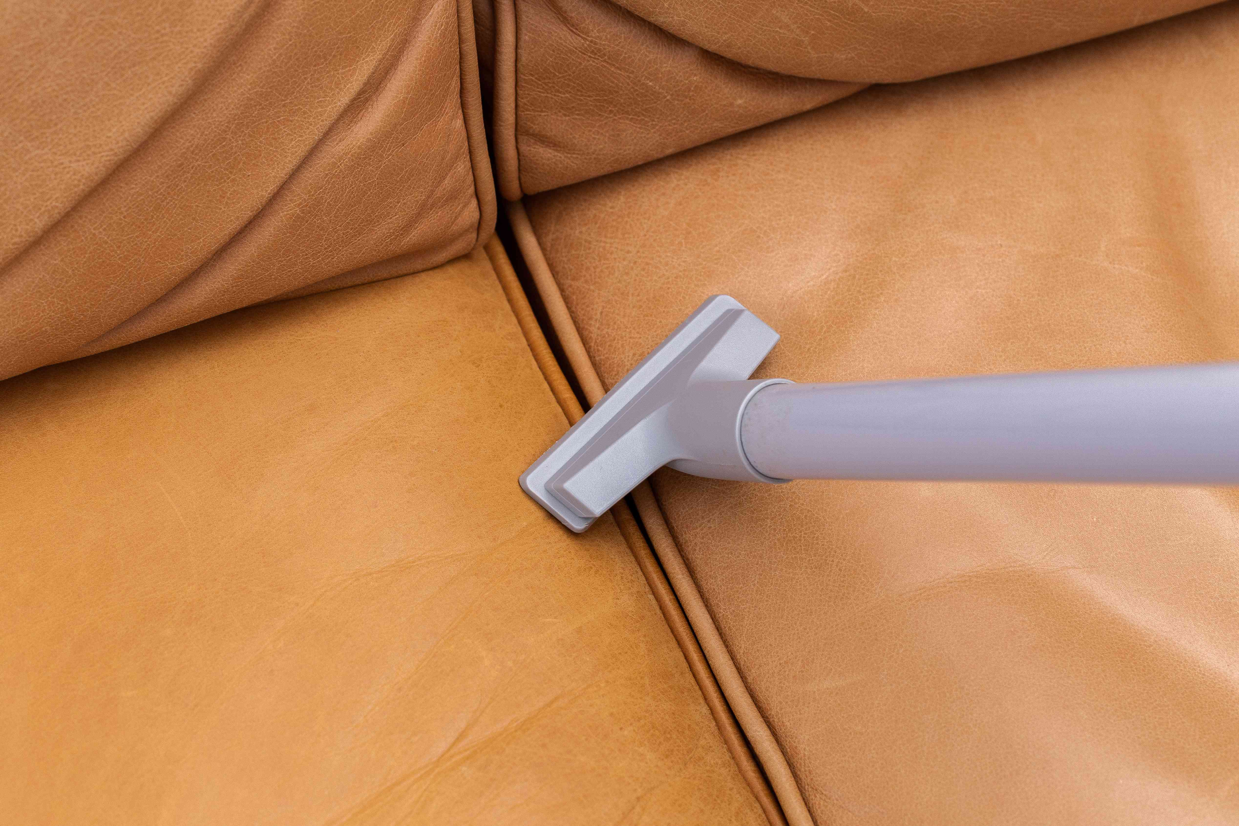 Vacuum with upholstery brush cleaning in between brown leather couch