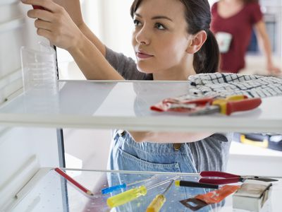 Woman Repairing Her Own Refrigerator