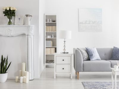 Lamp on cabinet and bookshelf next to grey sofa in white flat interior with painting and flowers. Real photo