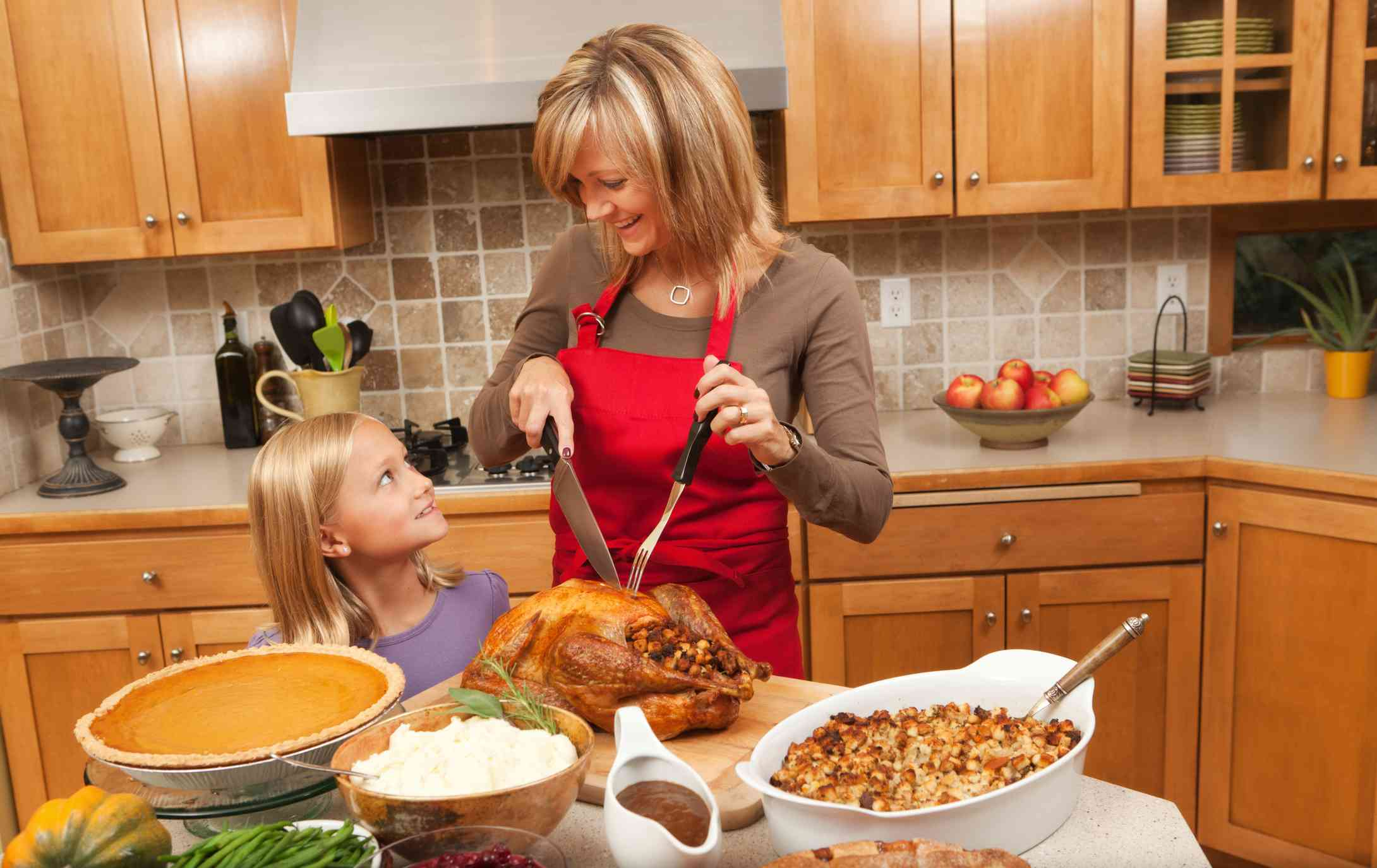 A mother and daughter carving a turkey in the kitchen