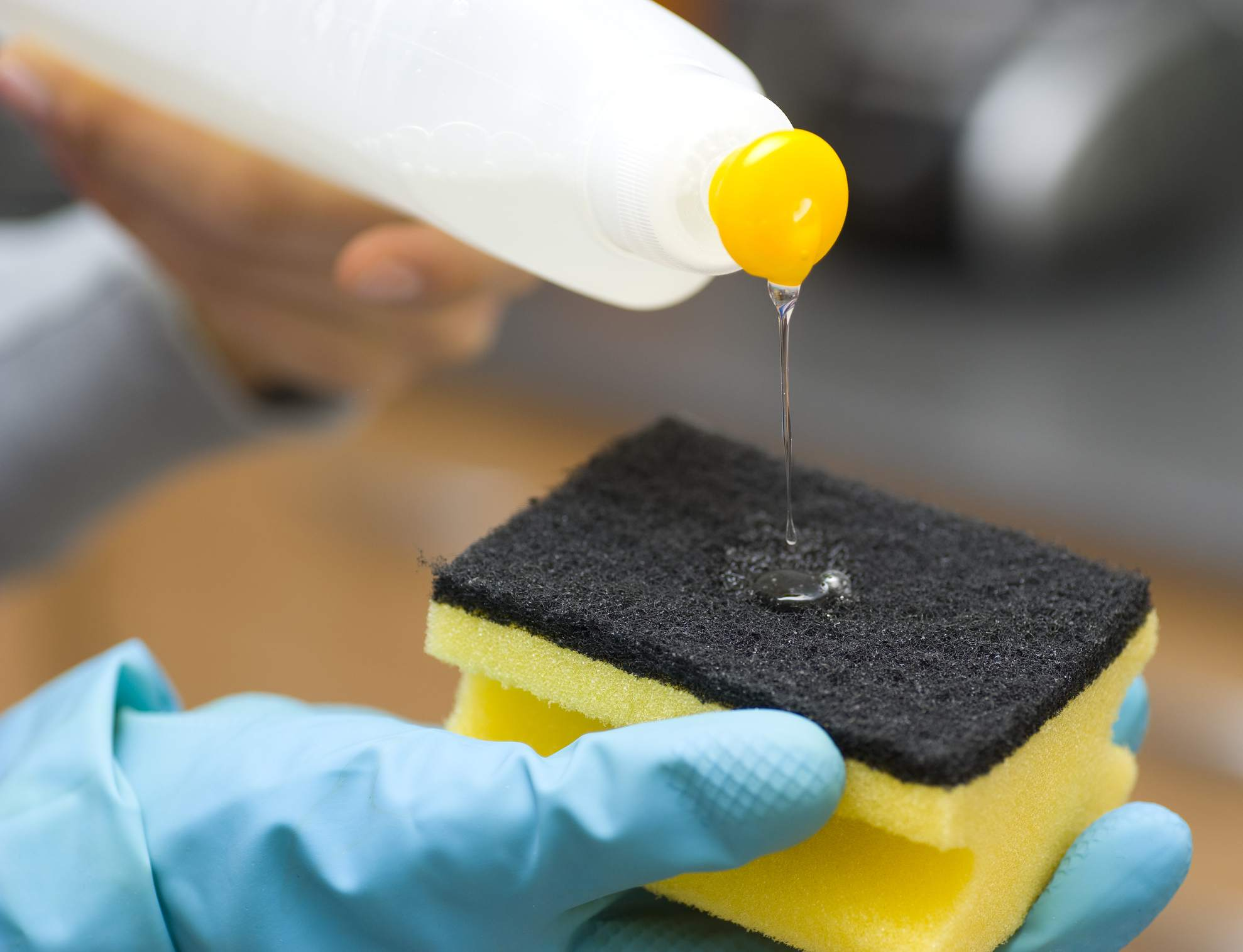 Squeezing dish soap into sponge