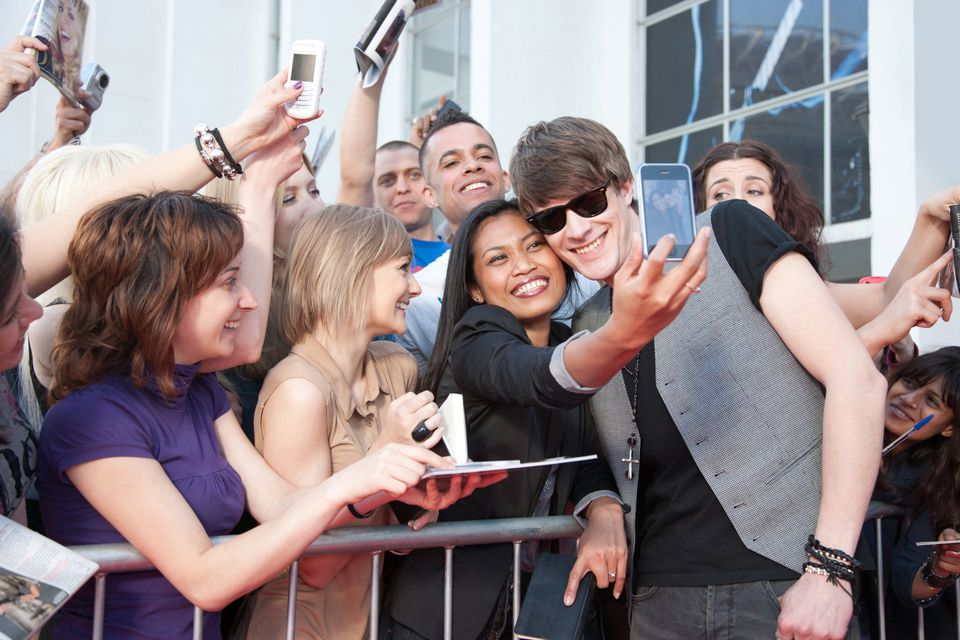 Fans taking pictures with a celebrity