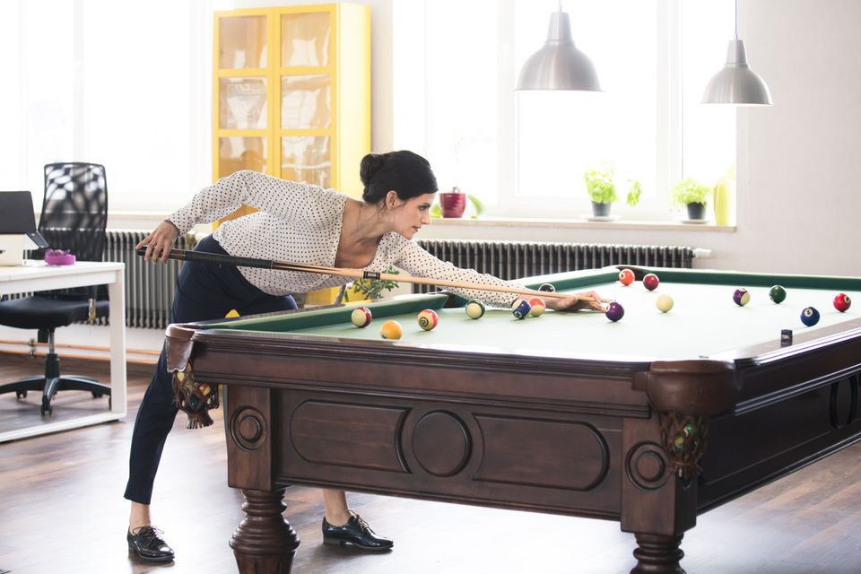 Determined businesswoman playing pool billard in modern office