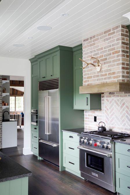 gabinetes de cocina verdes con placa para salpicaduras de ladrillo