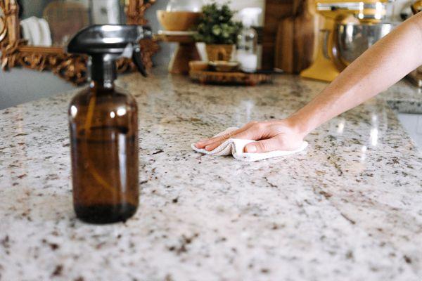 person wiping a granite countertop