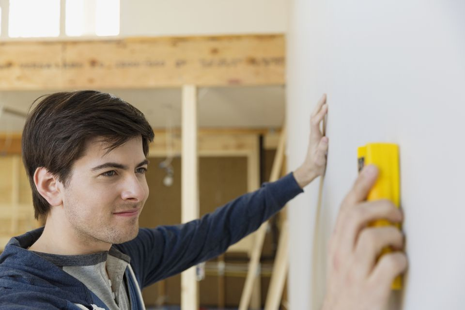 Young man with stud finder examining wall at home