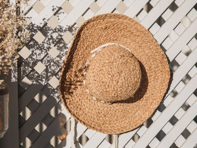 A straw hat hanging on a trellis