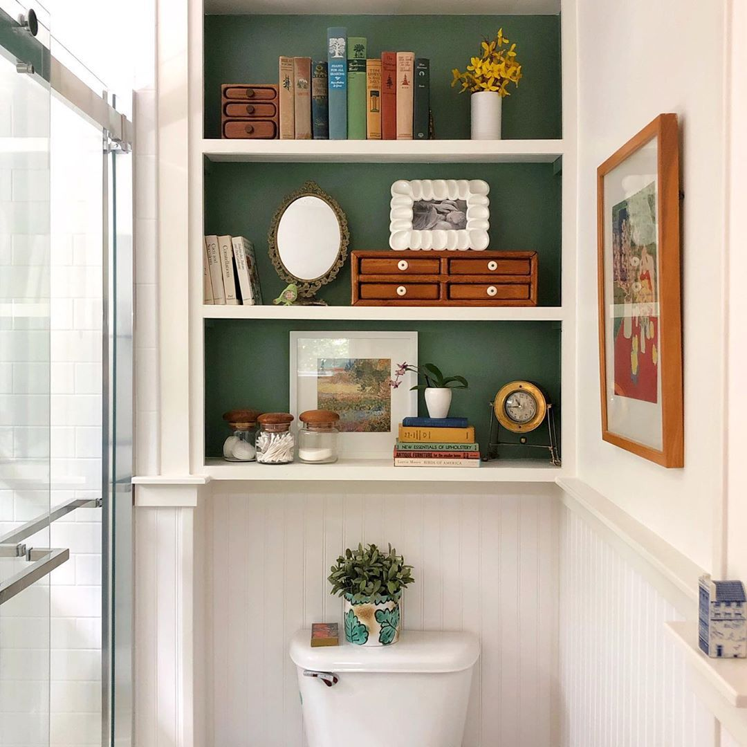 Green paint behind a bookshelf in a bathroom