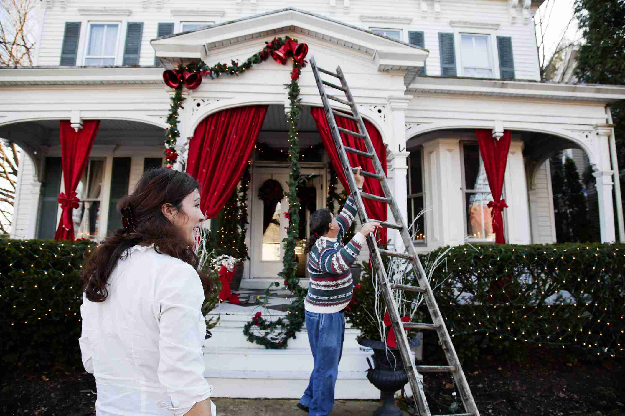 Couple hanging garlands on a house with a ladder for Christmas.