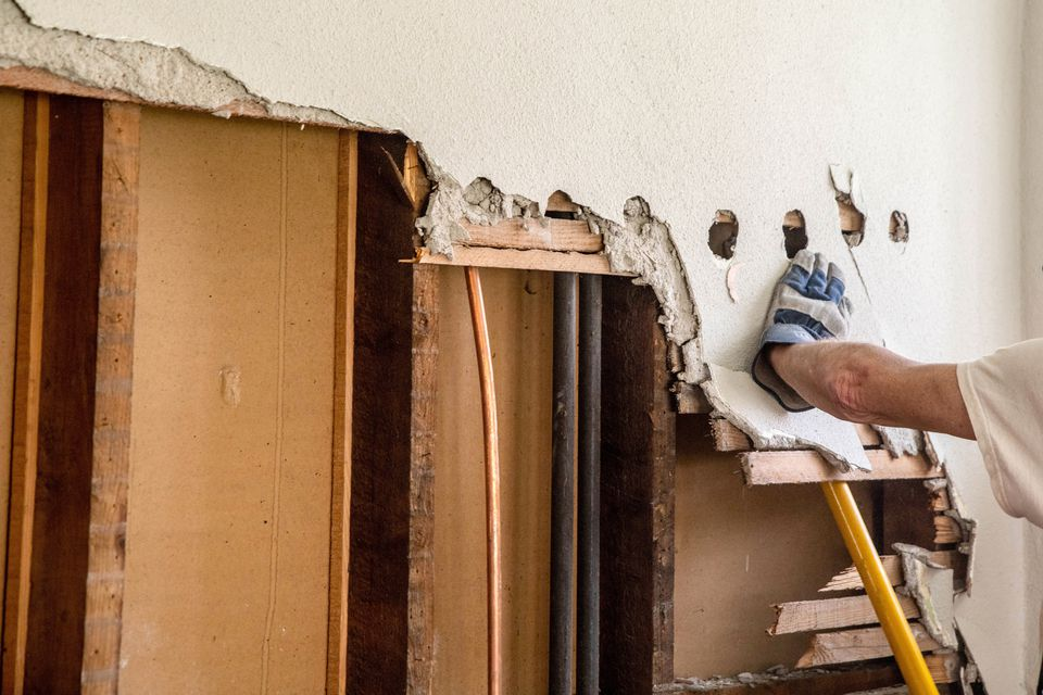 Load-bearing wall being removed for home renovation with yellow tool