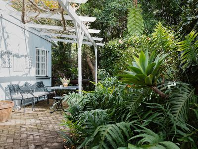 Shade garden with large ferns and plants next to white wood pergola over outdoor seating