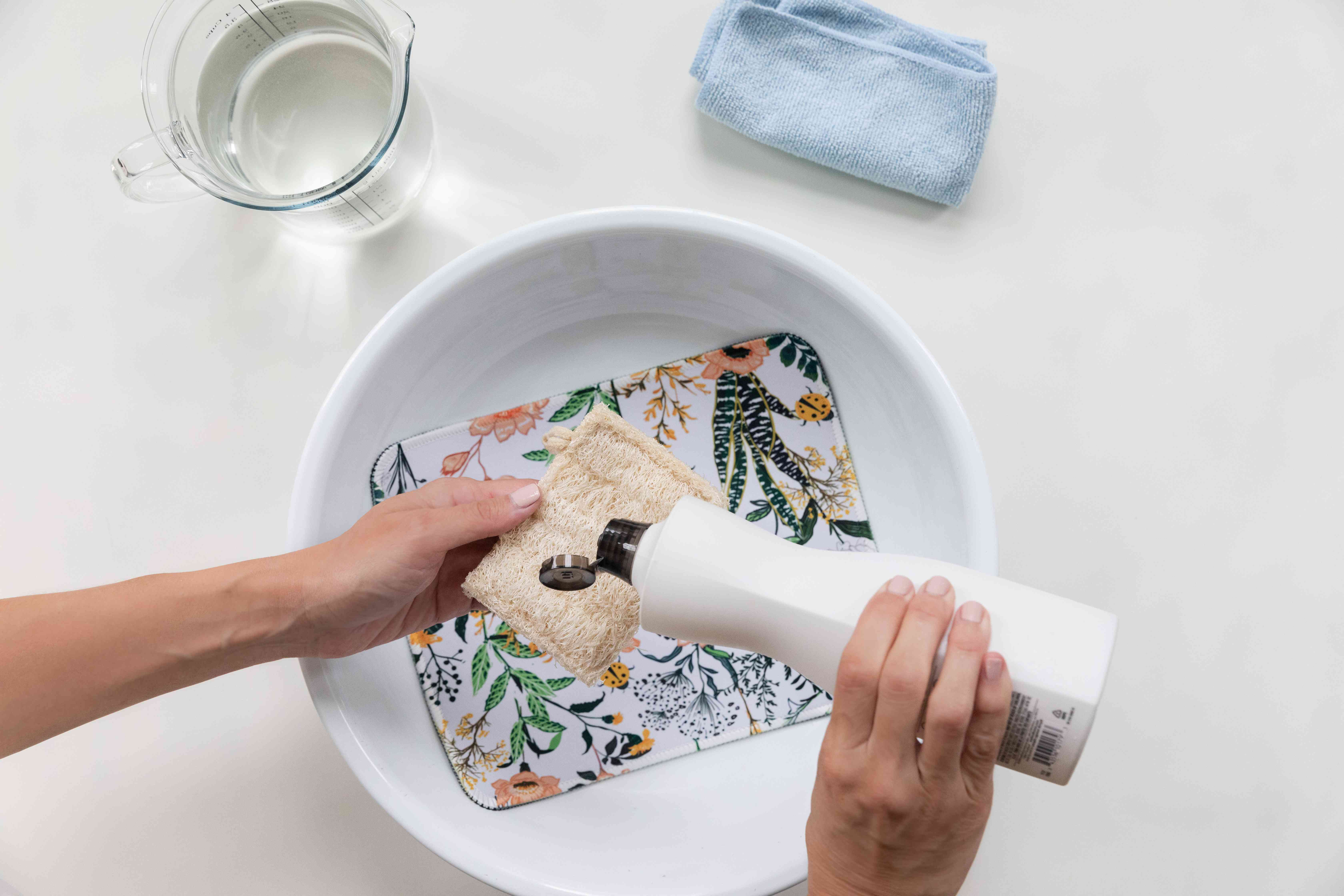 Dishwashing liquid added to tan sponge over floral mousepad in white container