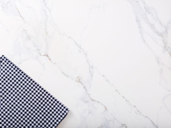 A plaid cloth on a marble surface.
