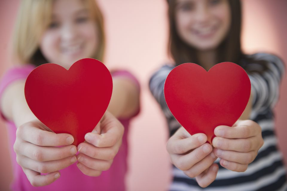 USA, New Jersey, Jersey City, Close up of two girl's hands holding red hearts