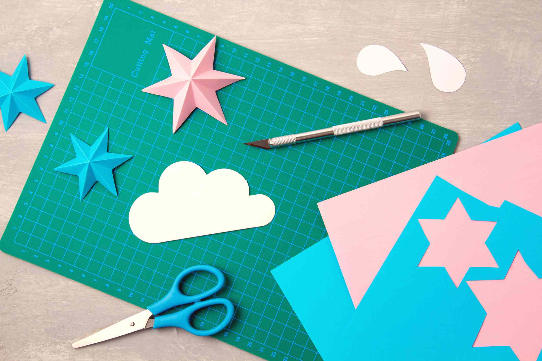 Top view over paper cut tools, scissors, cutter, cutting mat, and crafted paper objects. DIY trendy project concept