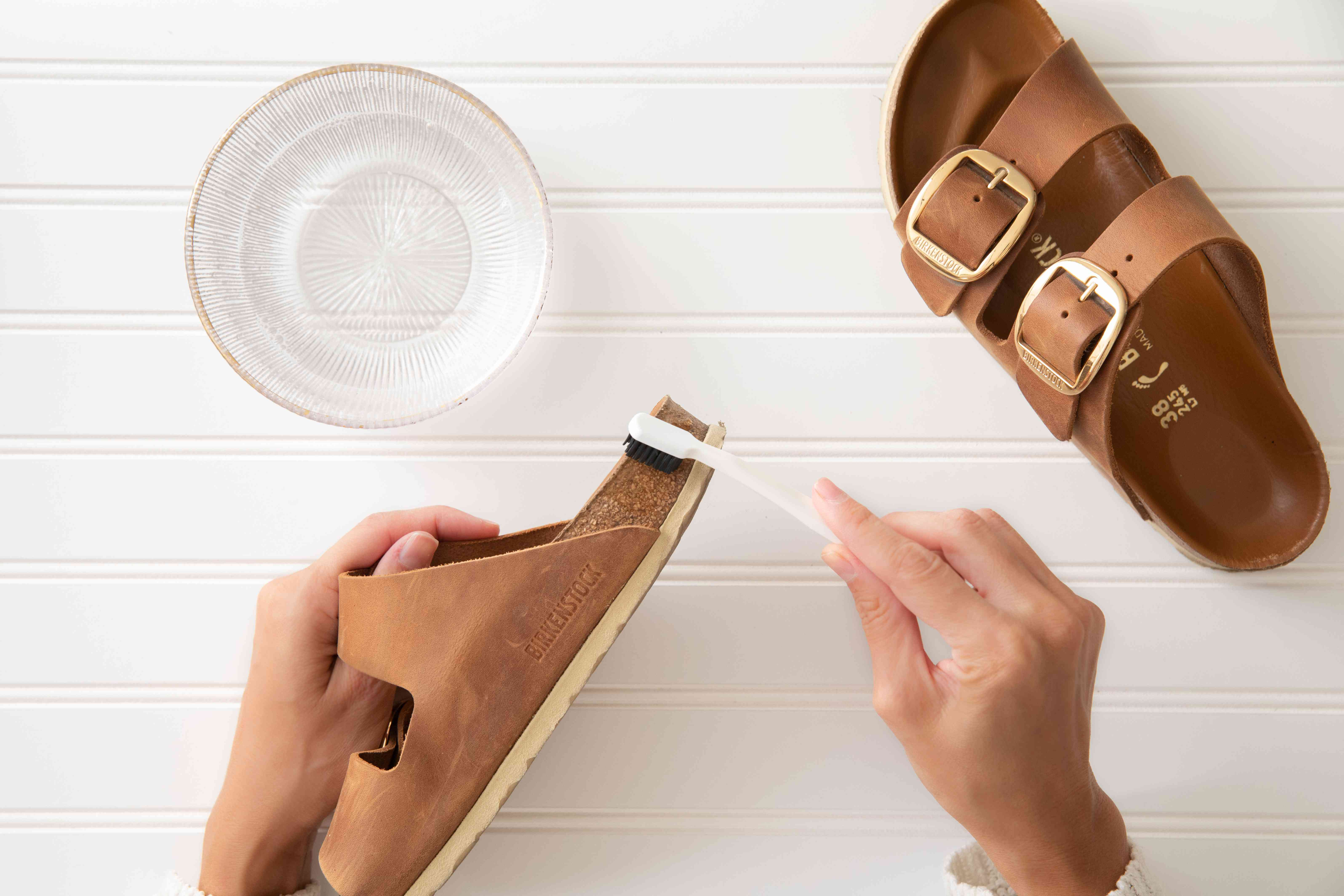 using an old toothbrush to gently scrub birkenstocks
