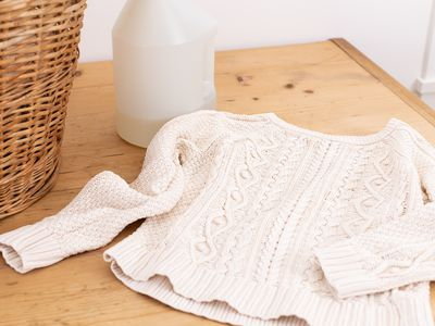 Wool sweater on wooden surface next to woven basket and plastic bottle