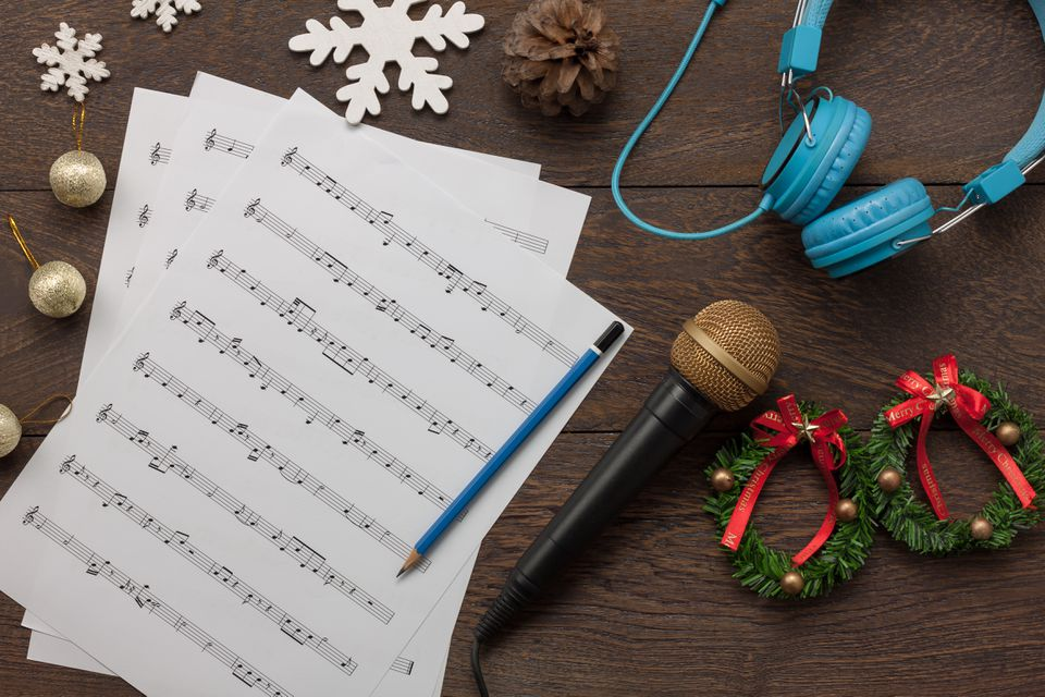 Table top view of music sheet note and accessories Merry Christmas & Happy new year concept.Instrument musical with decoration festive on the modern rustic dark brown wooden at home office desk.
