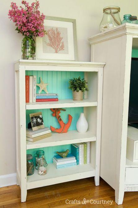 Librería blanca con un fondo azul verdoso pintado