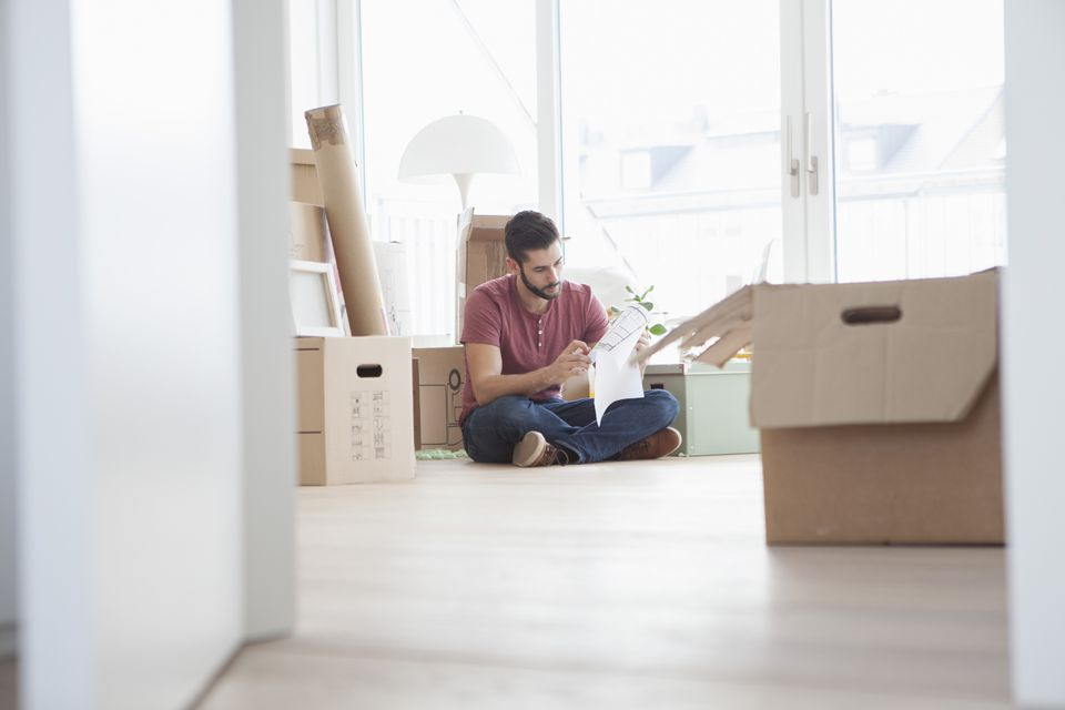 Young man in new flat with cardboard boxes holding ground plan