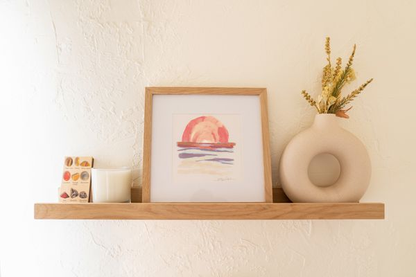 Upcycled wood shelving on white wall with framed print and small decor