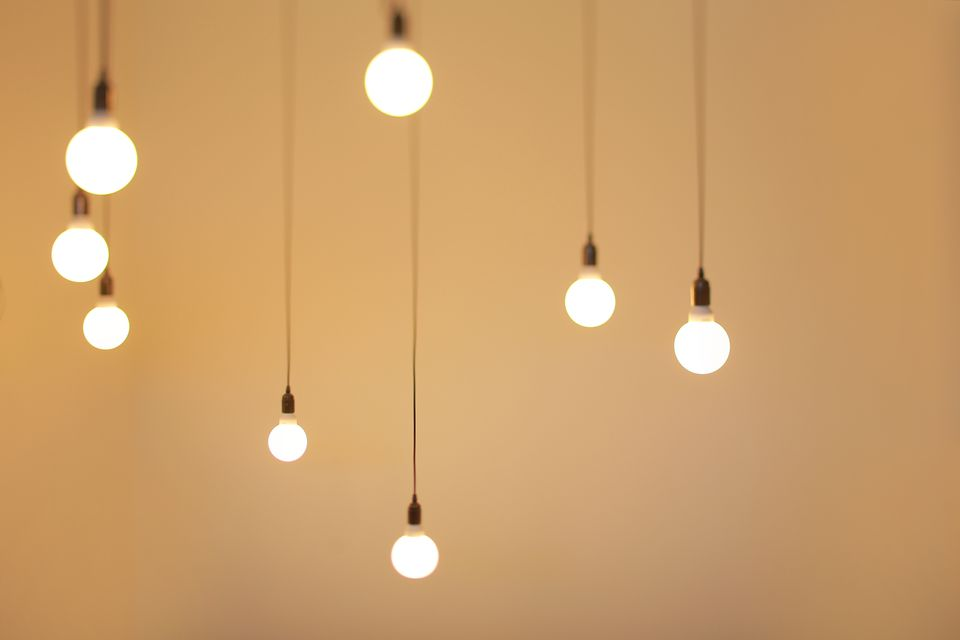 Illuminated Light Bulbs Against Beige Background