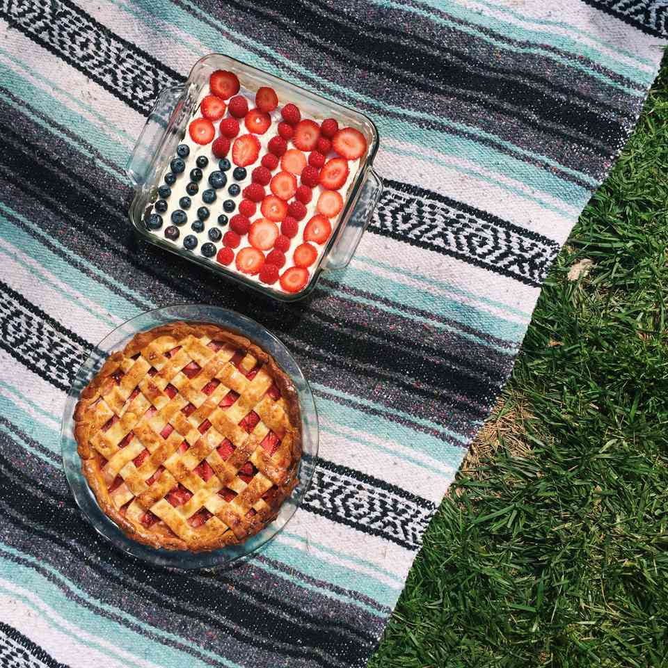 flag cake and strawberry pie on a picnic blanket
