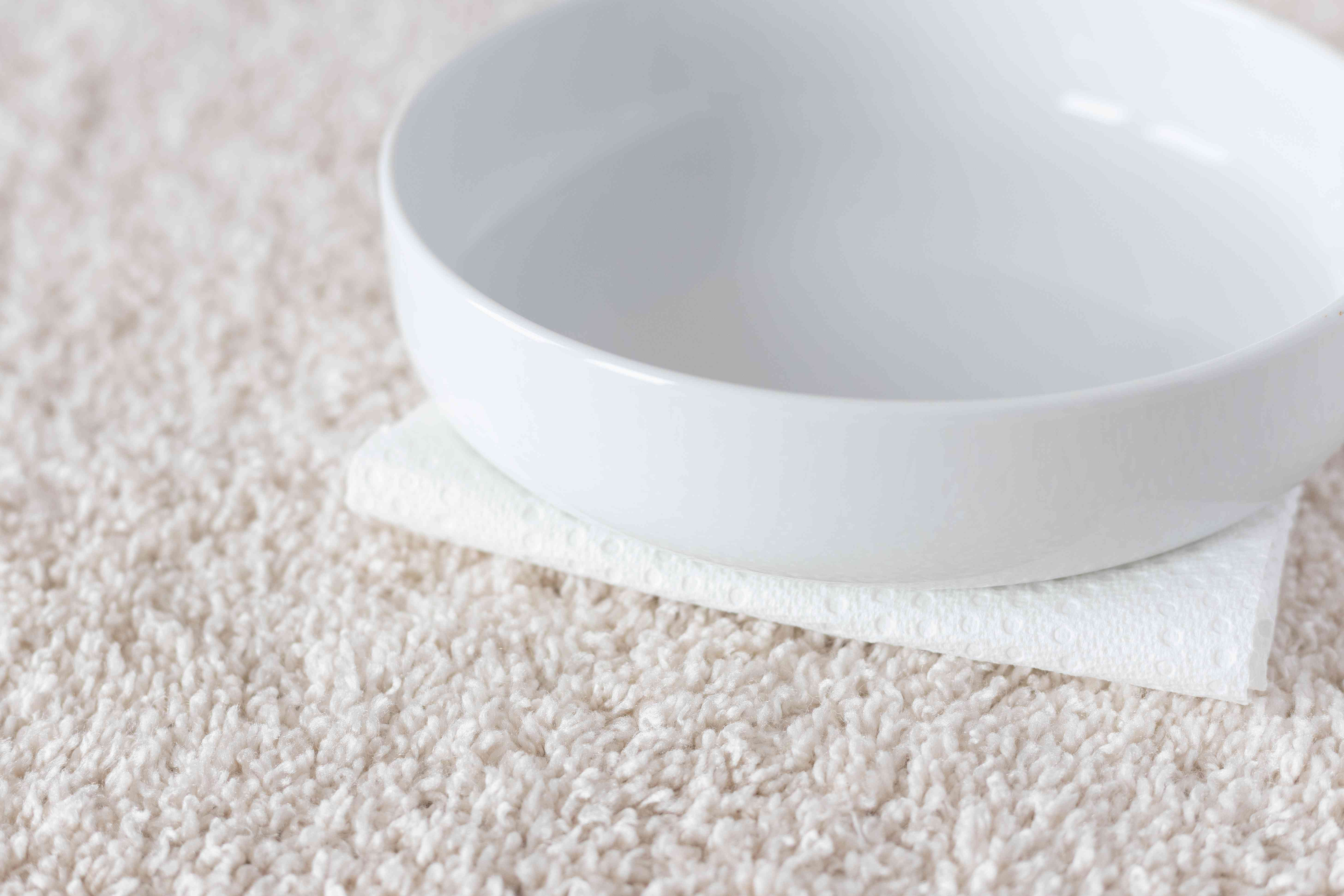 Folded paper towel weighed down by ceramic bowl on carpet