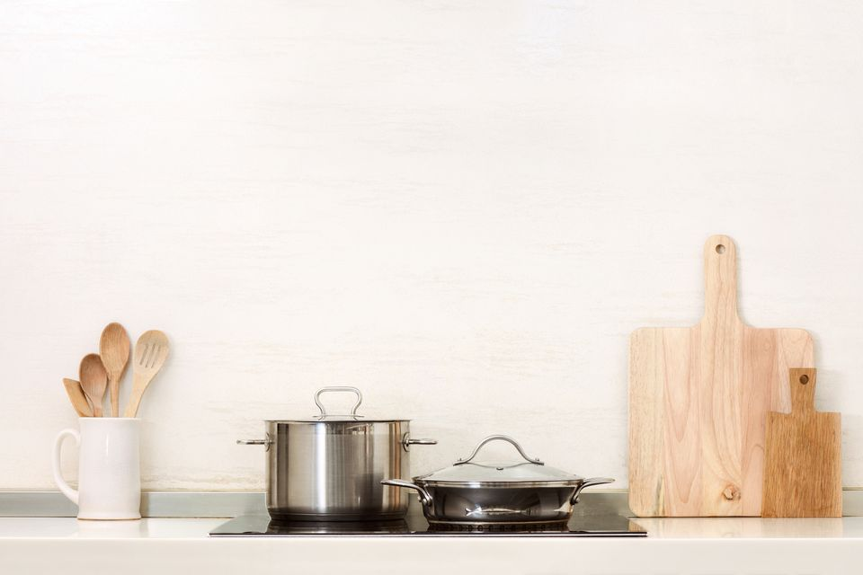 Two stainless steel pots on an electric stovetop with two cutting boards an a white cup full of wooden spoons.