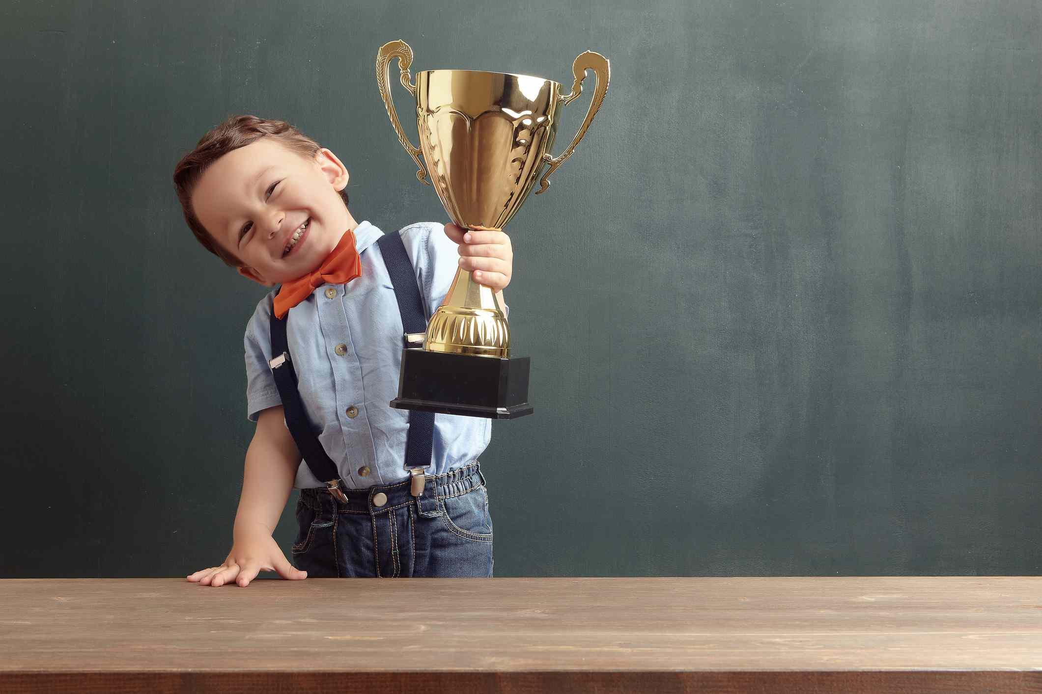 Little boy raising a golden trophy