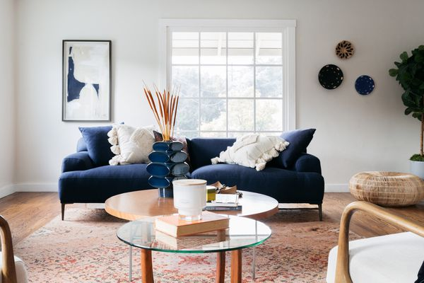 Navy blue couch and decor in living room with wooden and glass coffee tables
