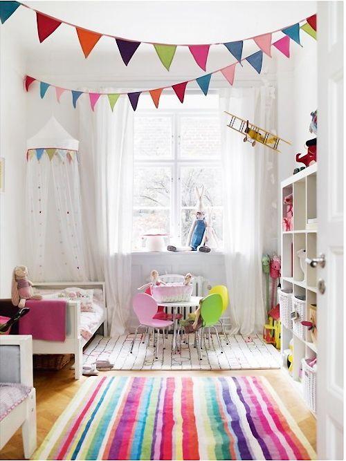 Blanco guardería con acentos de colores brillantes que incluyen una alfombra y colgantes que cuelgan del techo.