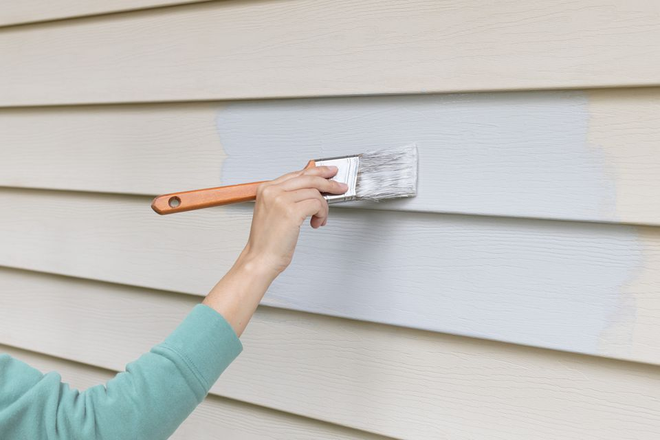 Light gray exterior paint sheen spread on outdoor wall panels with paintbrush