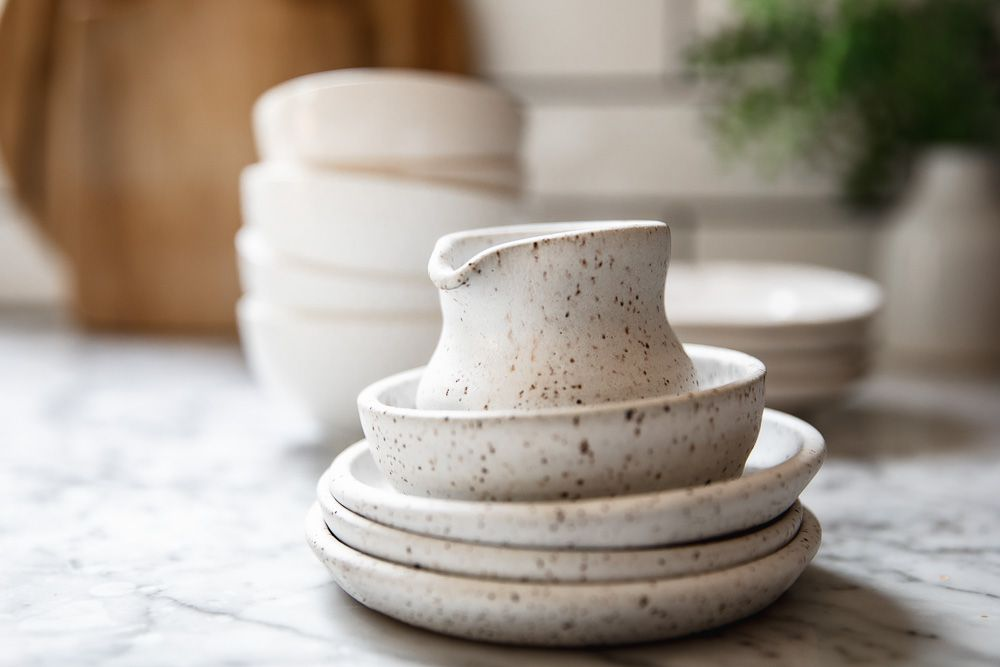 Stacked ceramic housewares on white surface to sell for cash