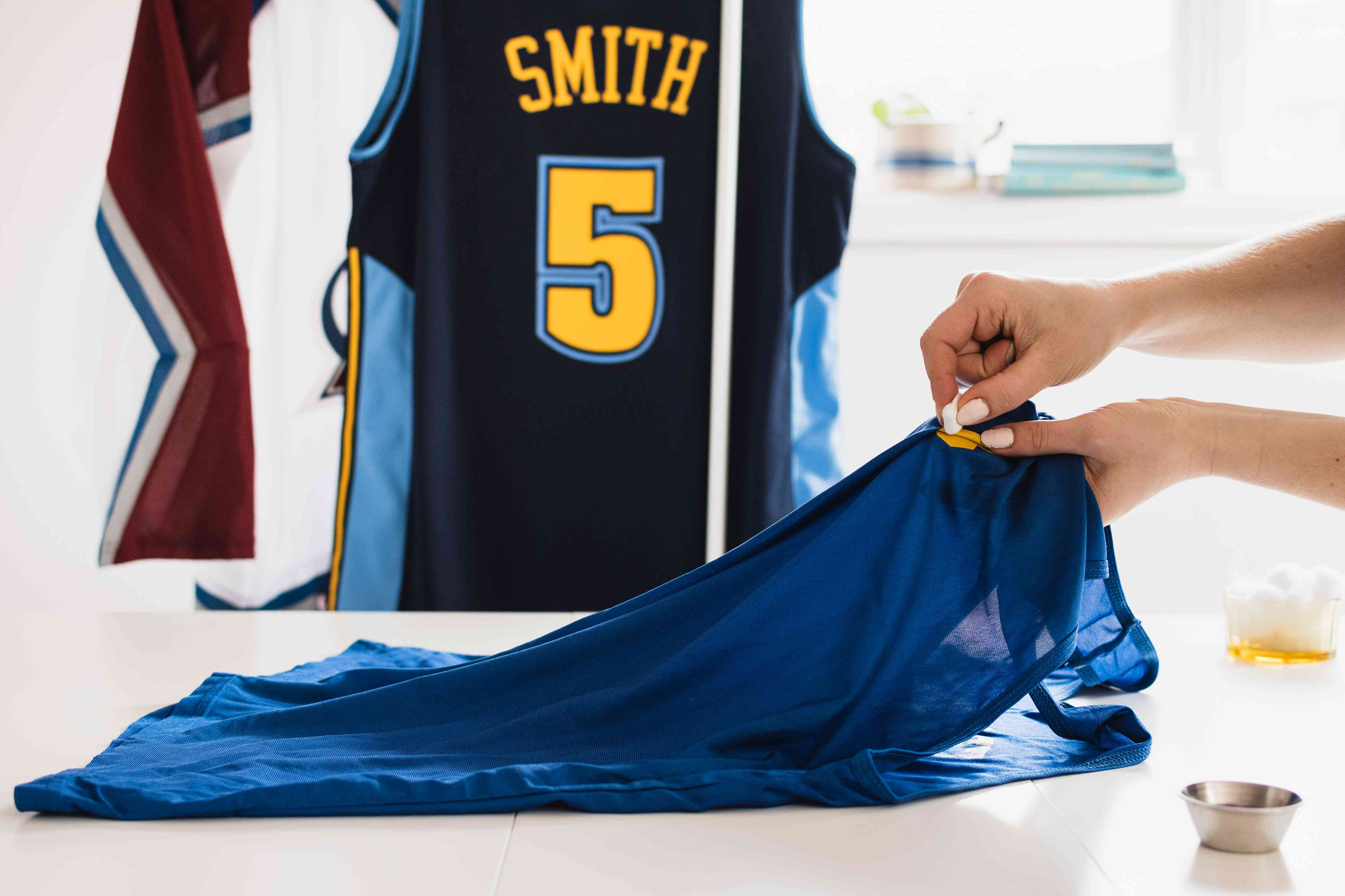 Separating melted lettering from team jersey with fingernail polish remover