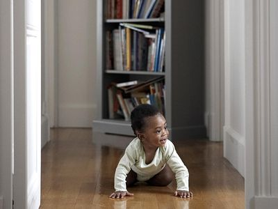 Baby crawling through hallway looking through door