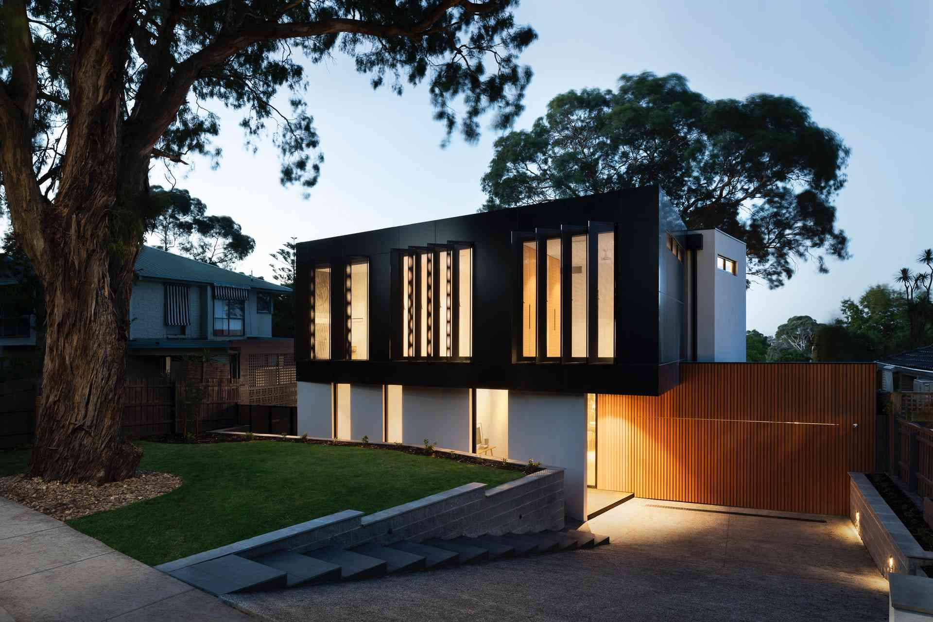 Modern architecturally designed home with a retaining wall contained front lawn