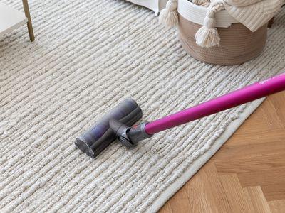 Pink vacuum passing over ruffled rug on wooden floor