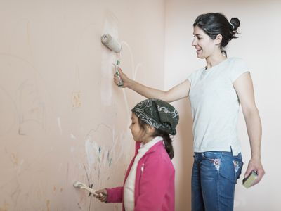 Mother and daughter painting wall in childrens room