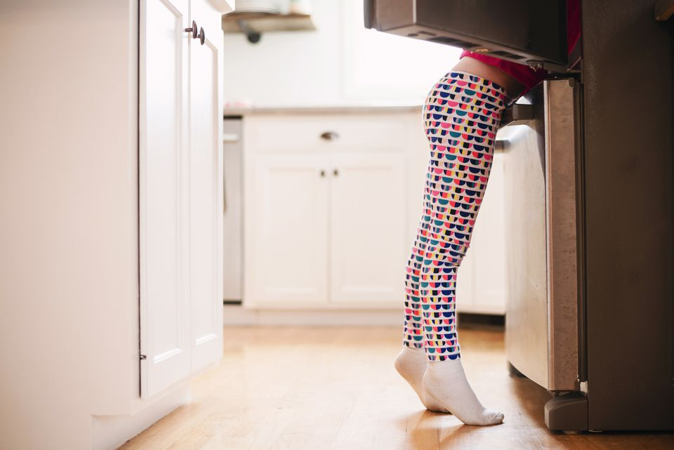 Girl standing by an open refrigerator