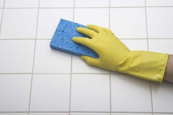 Person using rubber gloves and a sponge to clean tile.