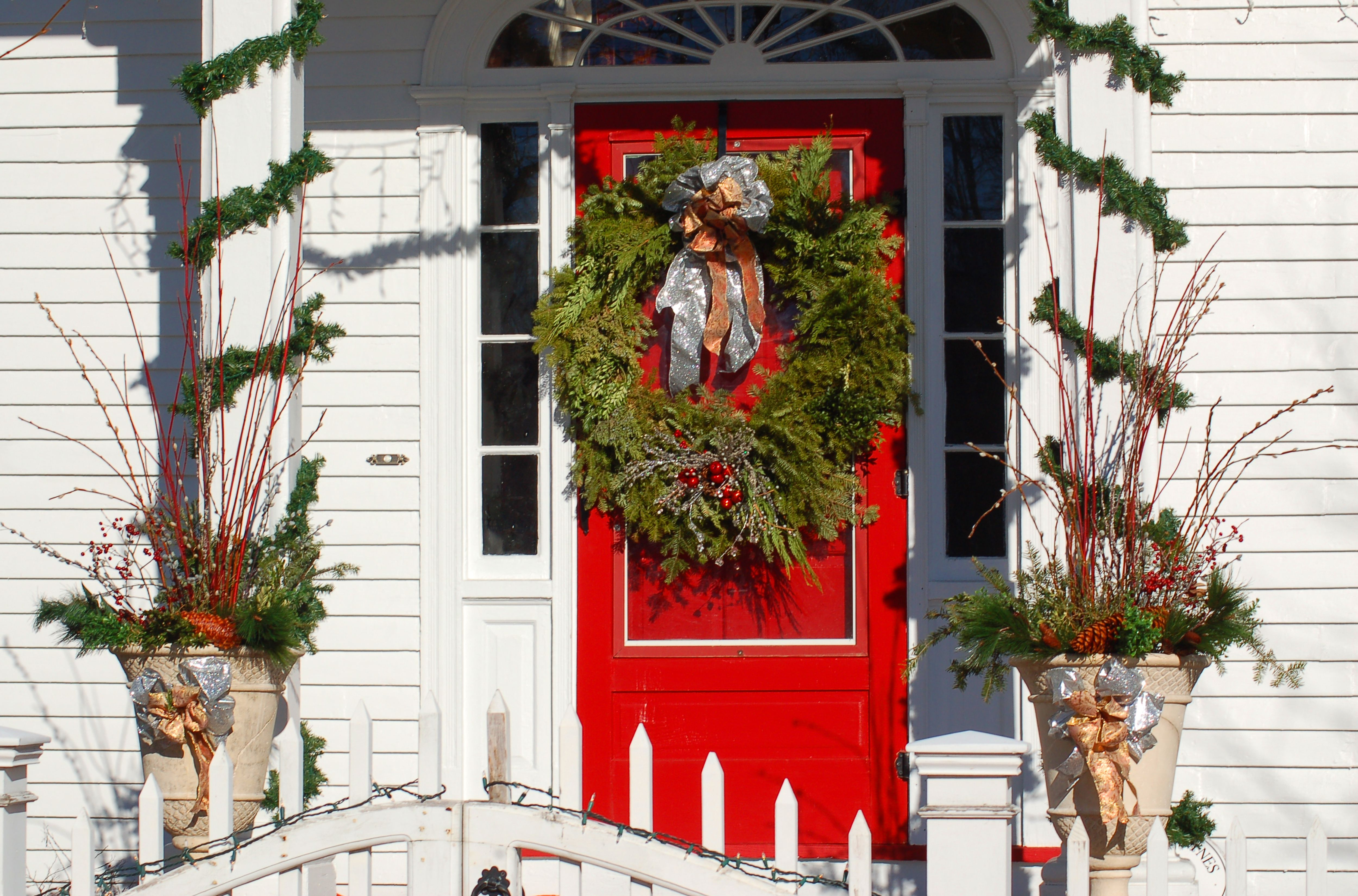 Columns with garlands and urns with Christmas decorations flanking a front door with a wreath.