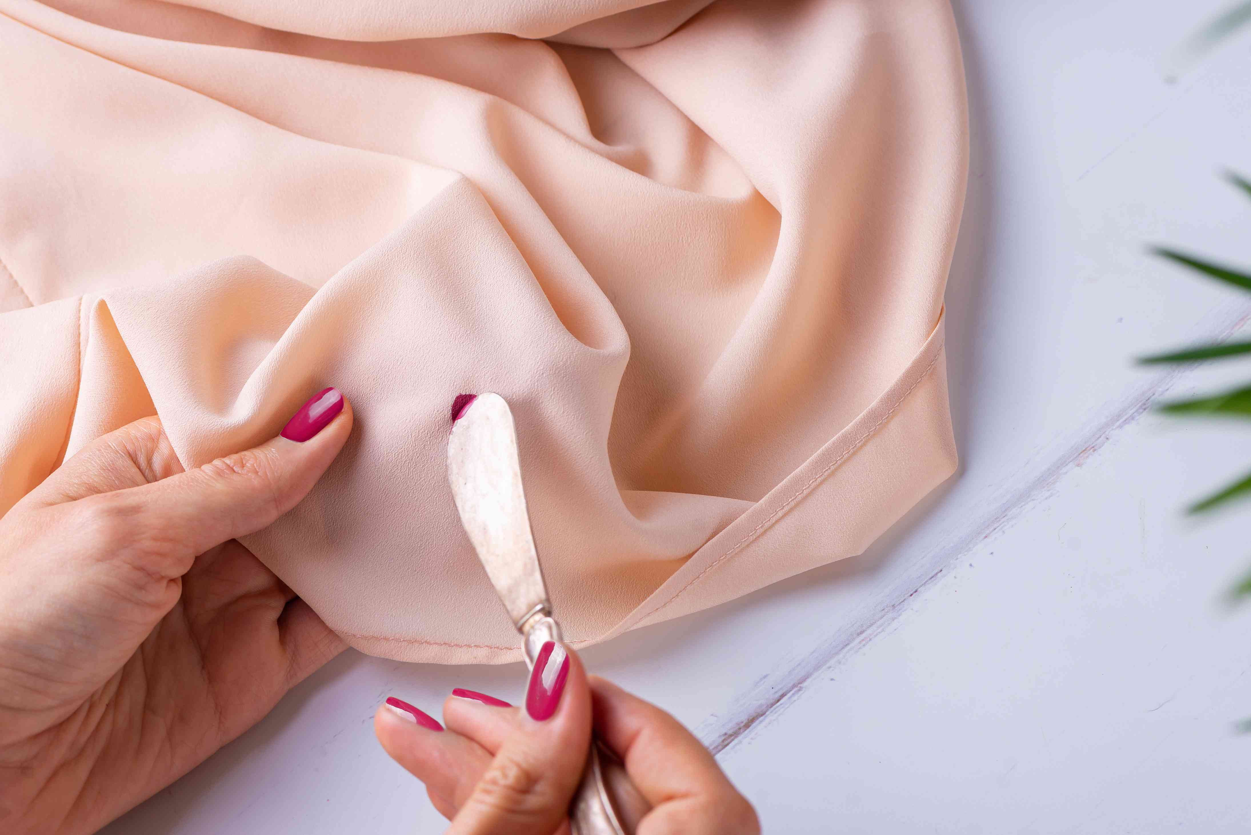 removing extra nail polish with a dull knife