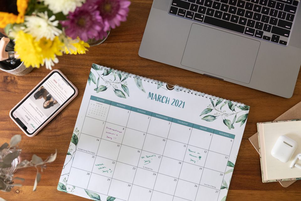 Calendar showing the month of march next to laptop and mobile phone on wooden surface