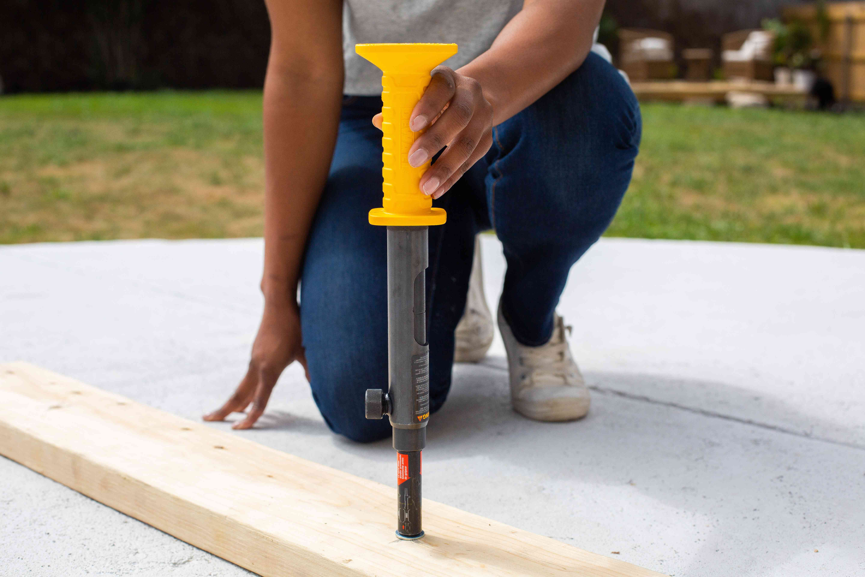 Concrete nail gun placed perpendicular to wooden board