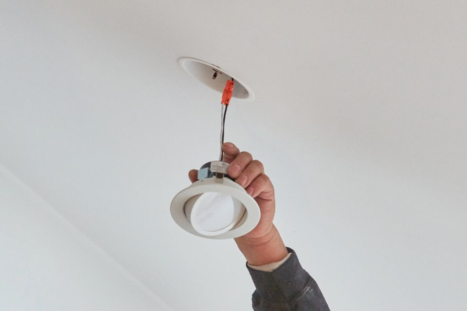 Can light fixture hanging by clasped wire in ceiling and hand holding canister