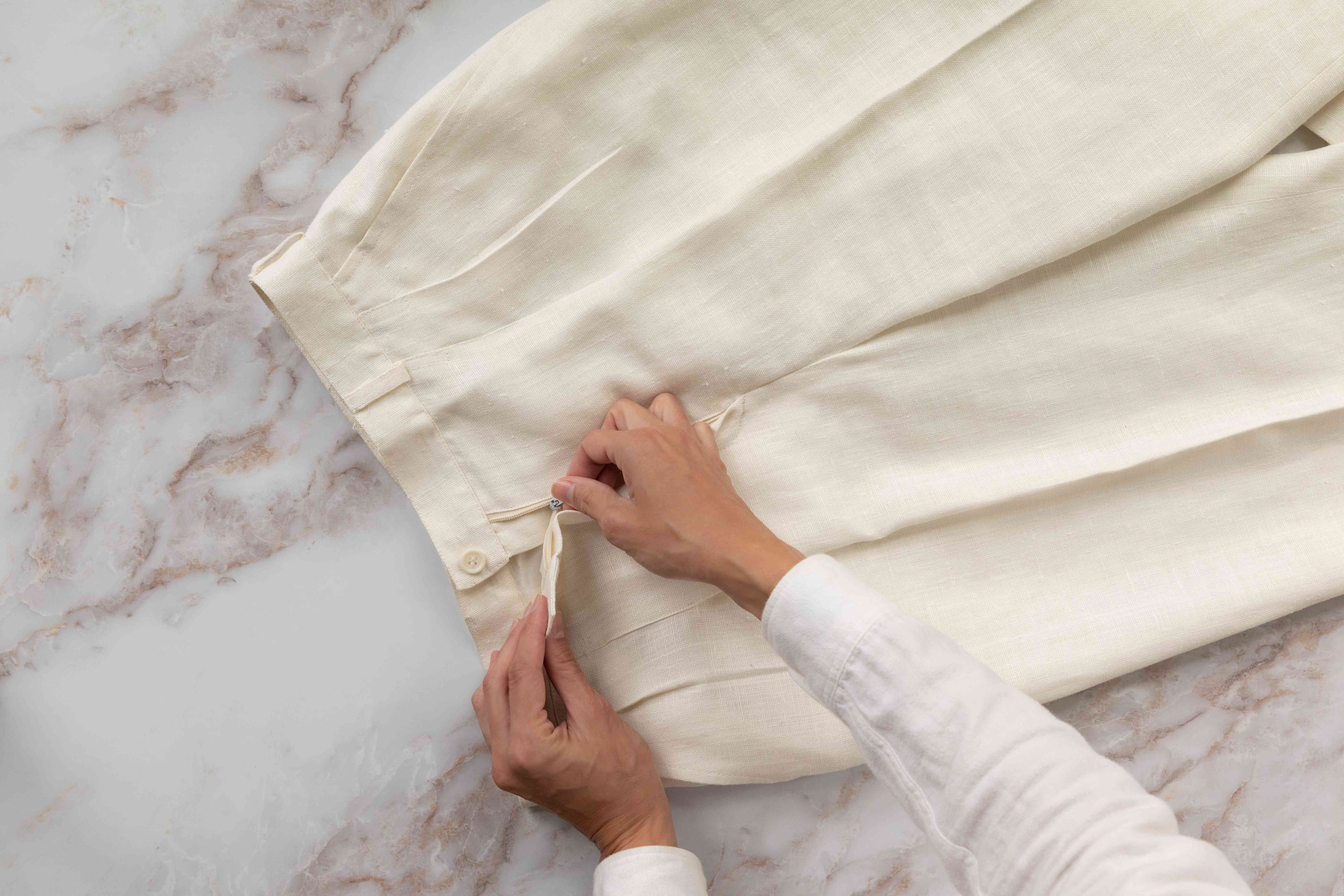 Cream-colored pants with creases laid on white marbled surface being zipped up
